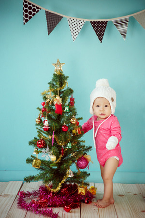 decorating christmas tree: Baby wearing white knitted beanie in front of blue background and Decorating Christmas tree on green background Stock Photo