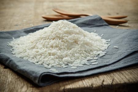 arroz blanco: Granos de arroz sin cocer en la tela con cuchara de madera y el folk - enfoque suave Foto de archivo