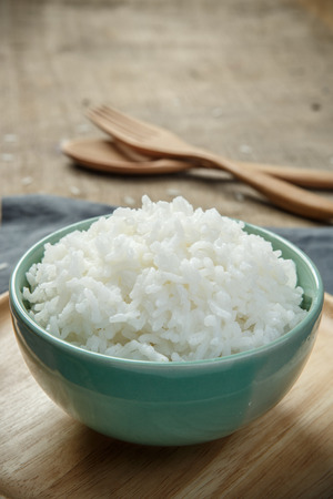 Cooked rice with a spoon and fork on wooden table - soft focus
