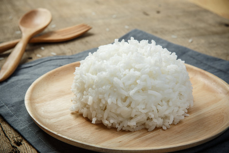 rice plate: Close-up view of cooked white rice with napery and wooden spoon - soft focus Stock Photo