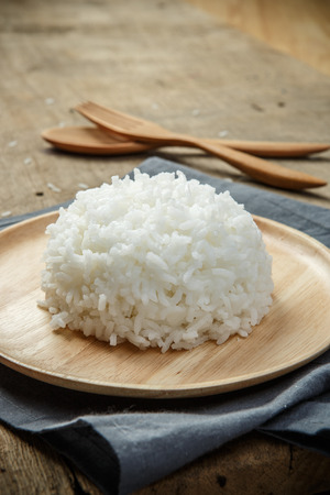 cooked: Organic White Rice in wooden dish on wooden table - soft focus Stock Photo