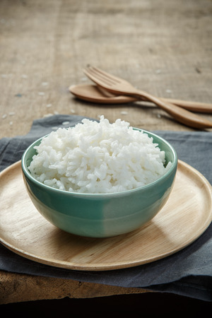 Thai jasmine rice in ceramic cup with napery and wooden spoon - soft focus