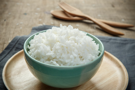 Bowl full of rice on the wooden table - soft focus