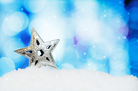 focus shot: Star and christmas decoration on abstract background and snowflakes - selective focus shot