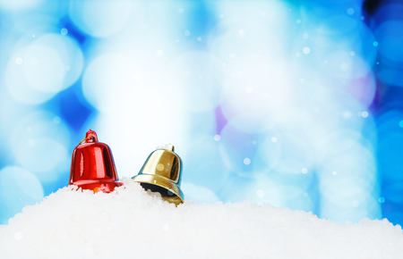 focus shot: Bell and christmas decoration on abstract background and snowflakes - selective focus shot
