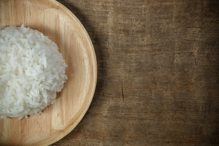 Organic White Rice in wooden dish on wooden table - soft focus Stock Photo