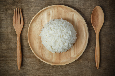 Top view of Thai jasmine rice in wooden dish with napery and wooden spoon - soft focus