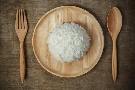 arroz chino: Vista superior de arroz jazmín tailandés en plato de madera con mantelería y cuchara de madera - enfoque suave