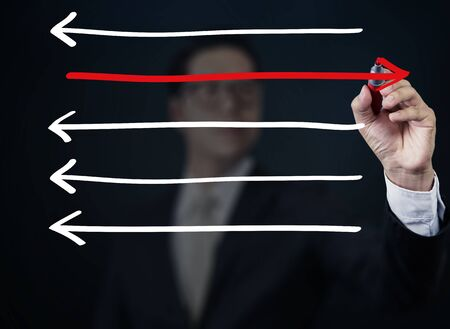 way out: Businessman drawing arrows in different directions, business collection, studio shot Stock Photo