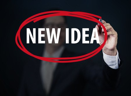 new idea: Businessman hand writing NEW IDEA with red marker on transparent board, new business concept, studio shot Stock Photo