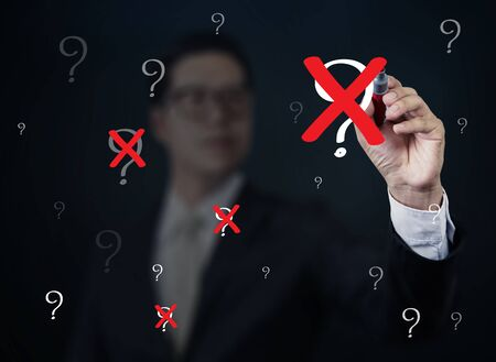 neutralize: Businessman hand writing Question with red marker on transparent board, new business concept, studio shot Stock Photo