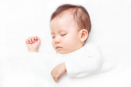 Pasgeboren slapen op het witte bed (geïsoleerd op een witte achtergrond) Stockfoto - 68117361