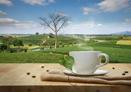 Taza de café con saco sobre la mesa de madera y el fondo Plantaciones