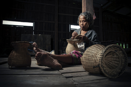 poverty: Asian grandmother fisherman with the net bamboo Stock Photo
