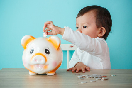 little baby moneybox putting a coin into a piggy bank - kid saving money for future concept Banque d'images