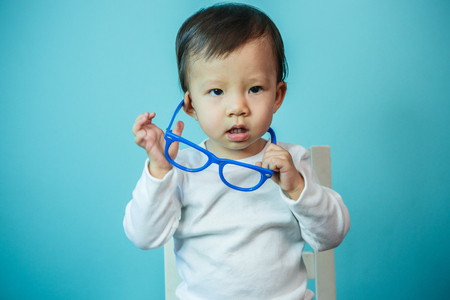 geen: Baby happy wearing glasses on the blue background, new family and love concept (soft focus on the eyes) Stock Photo