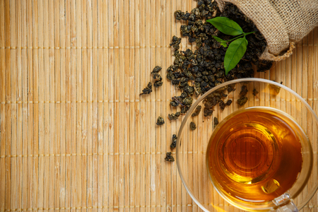 Tea and leaves tea on bamboo placemat