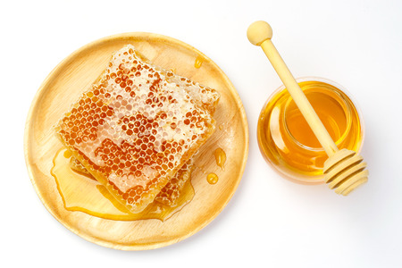praiseworthy: Sweet honeycomb and wooden drizzler, isolated on white