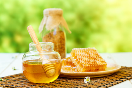 Honeycombs with jar and dipper on white wooden background 写真素材