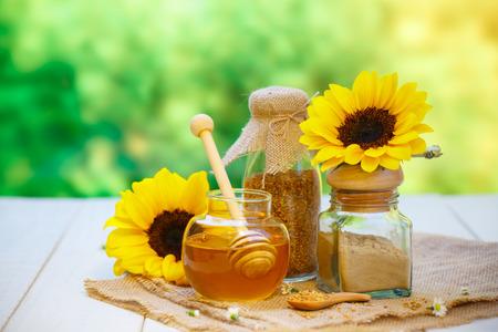 Bols en verre avec un autre miel avec du pollen et de la propolis. Louche de miel, cuillère, cire d'abeille, tournesol sur le fond en bois Banque d'images - 68117427