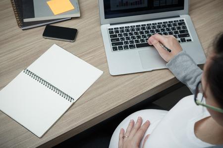 madre trabajando: mujer embarazada hermosa joven que trabaja con el ordenador portátil