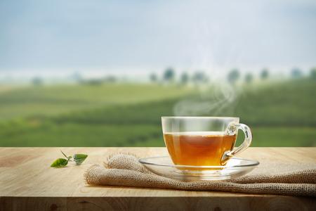 taza de té: Taza de té con la hoja de té despedida en la mesa de madera y las plantaciones de té de fondo Foto de archivo