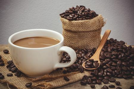 capuchino: Taza de café caliente con granos de café en la mesa de madera y el fondo negro, efecto de color de estilo vintage Foto de archivo
