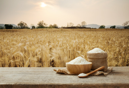 Jasmine Rice in bowl and burlap sack on wooden table with the golden rice field background