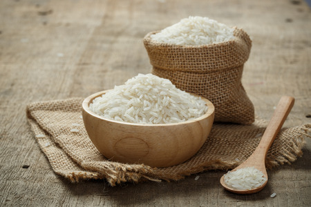 Jasmine Rice in bowl and burlap sack on wooden table Stockfoto