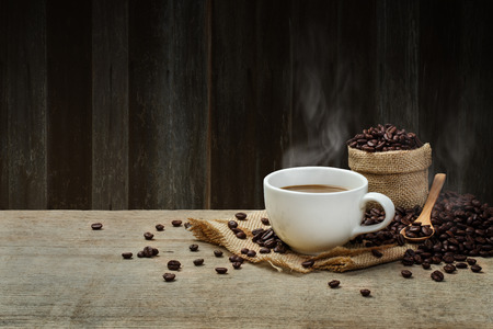 Hot Coffee cup with Coffee beans on the wooden table and the wooden wall Foto de archivo