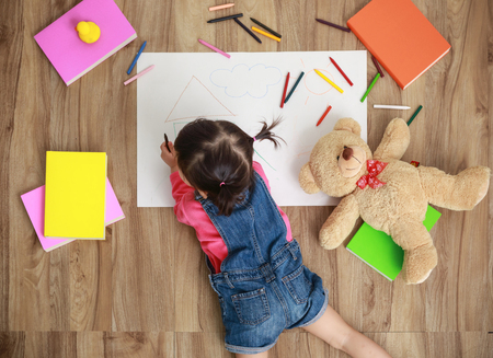 Little Asian girl drawing in paper on floor indoors, top view of child on floor Stockfoto