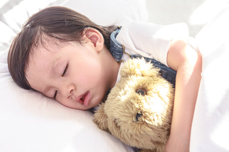 그녀의 장난감 곰 잠자는 작은 아시아 소녀