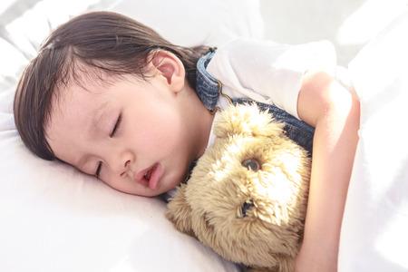 Little asian girl sleeping with her toy teddy bear