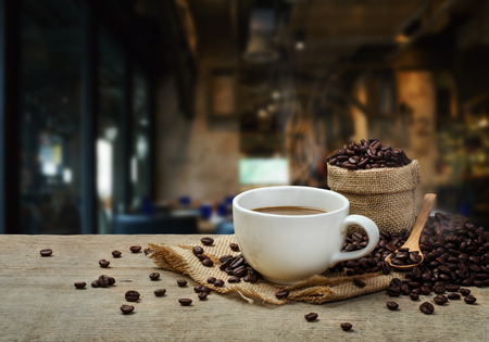 Hot Coffee cup with Coffee beans on the wooden table and the coffee shop background