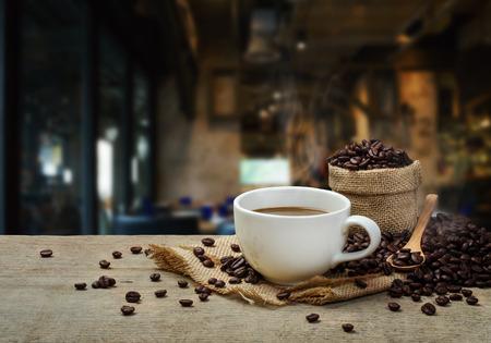 Taza de café caliente con granos de café sobre la mesa de madera y el fondo cafetería Foto de archivo - 68128784