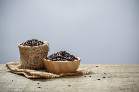 Black Rice on wooden table Stock Photo