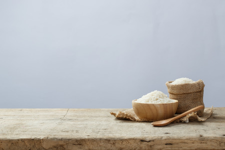 Jasmine rice in bowl and sack on wooden table