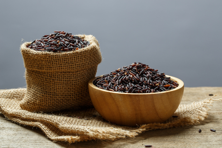 Rice berry or uncooked brown rice in bowl and burlap sack on wooden table