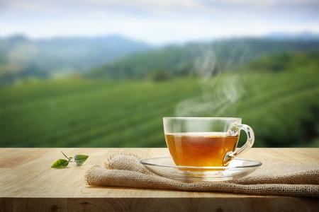 Taza de té con la hoja de té despedida en la mesa de madera y las plantaciones de té de fondo