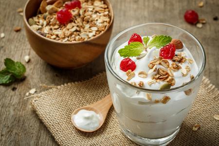 llanura: Yogur griego en un vaso con cucharas sobre fondo de madera