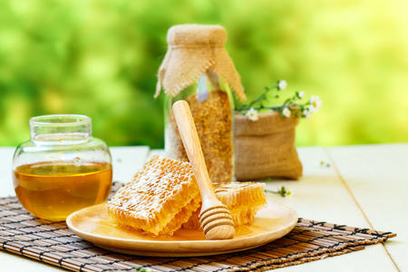 wooden stick: Honeycomb with jar and bee pollen on white wooden background Stock Photo