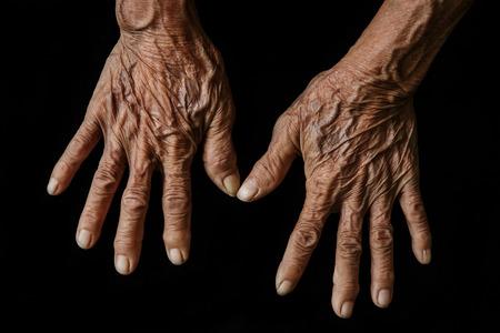 Old hands on a black background