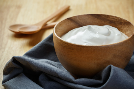 yogurt natural: Yogurt in wooden bowl on wooden background with blue cotton and wooden spoon. plain yoghurt. yogurt. yoghurt.