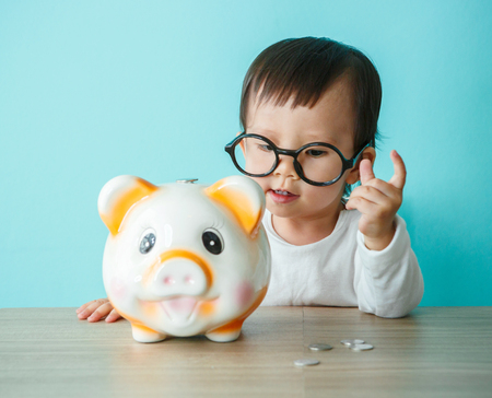 business money: little baby moneybox putting a coin into a piggy bank - kid saving money for future concept Stock Photo