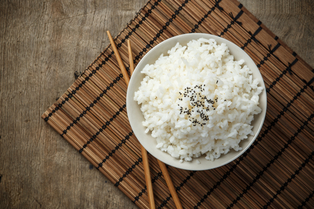 Steamed rice and black sesame seeds with chopsticks on a bamboo mat Stockfoto