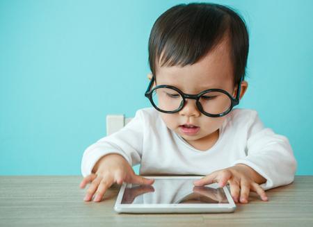 파란색 배경에 태블릿 pc에 작은 아기 스톡 콘텐츠
