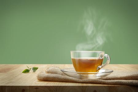 나무 테이블 및 녹색 배경에 약탈과 차 한잔
