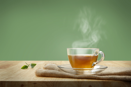 Cup of tea with sacking on the wooden table and green background