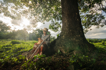 underdeveloped: Asian grandmother fisherman with the net bamboo under the big tree