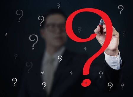Businessman hand writing Question with red marker on transparent board, new business concept, studio shot Stock Photo